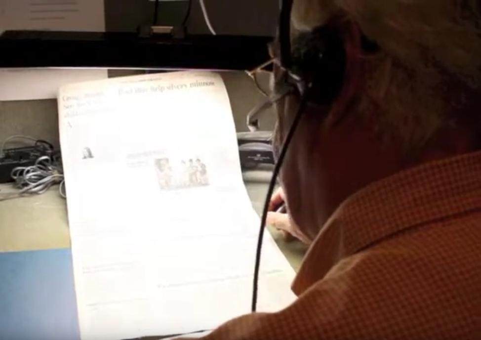 man transcribing newspaper into microphone